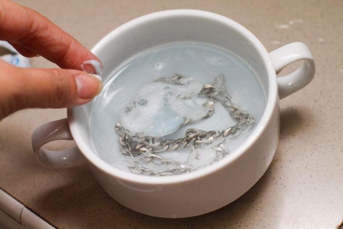 Процесс замачивания серебряного украшения в мыльном растворе
