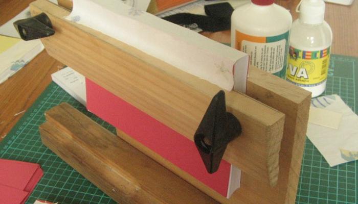 Закрепление книги в тисках для склеивания переплета